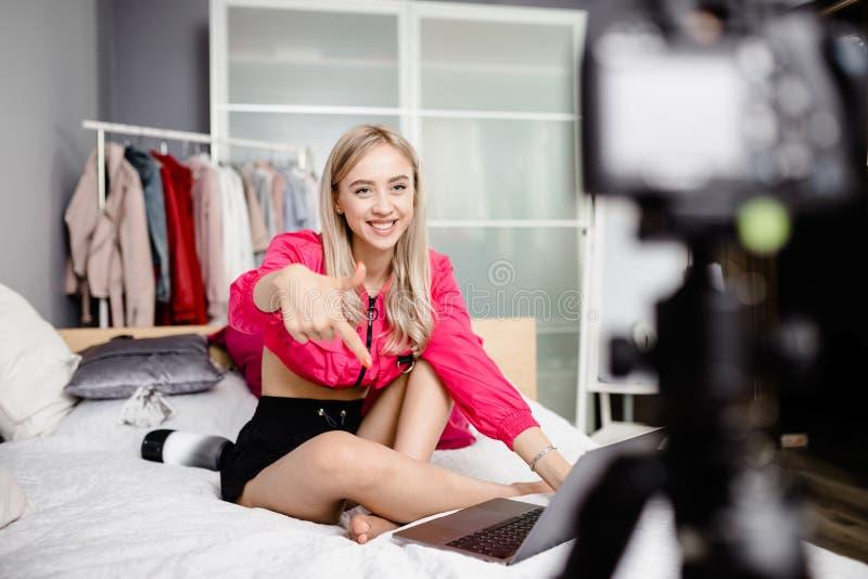 Het mooie jonge meisje blogger kleedde zich in heldere modieuze kleren die op het bed met laptop zitten en video maken royalty-vrije stock afbeelding