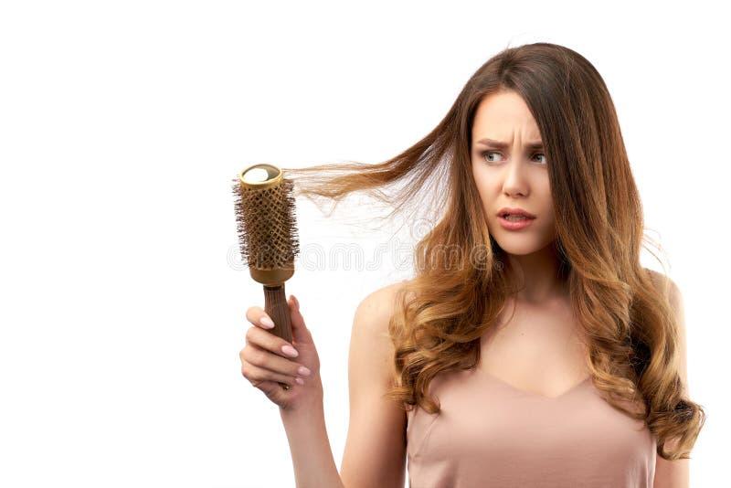 Het mooie jonge meisje die haar sloten, en met ontevreden kammen, teleurgesteld kijkt op gezicht vastbesloten bekijkend haarborst stock foto's