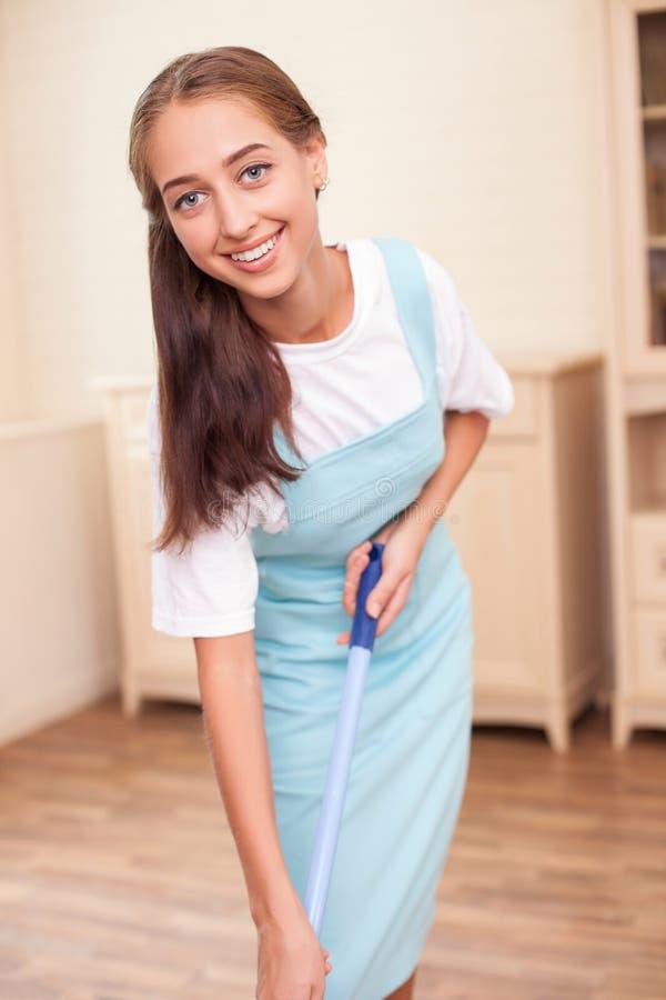 Het mooie jonge meisje doet schoonmaak met vreugde stock fotografie