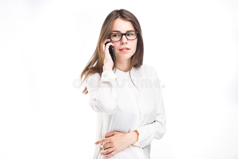 Het mooie jonge meisje in een wit overhemd op wit isoleerde achtergrond die op een mobiele telefoon spreken Glimlachenportret aan stock foto's