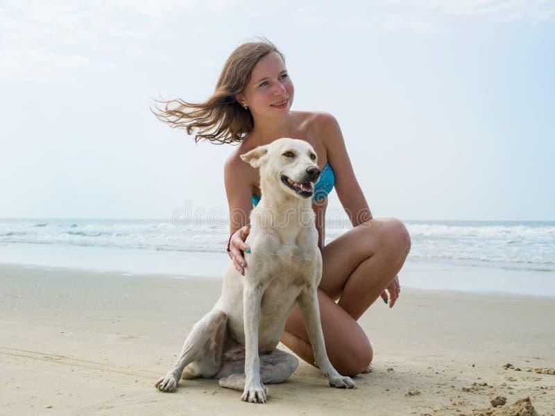 Het mooie jonge meisje in een zwempak koestert een witte hond op het strand door het overzees stock fotografie