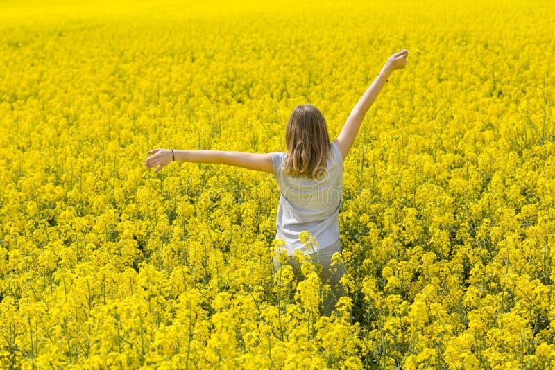 Het mooie jonge meisje geniet van de geur van geel bloemrijk gebied royalty-vrije stock afbeelding