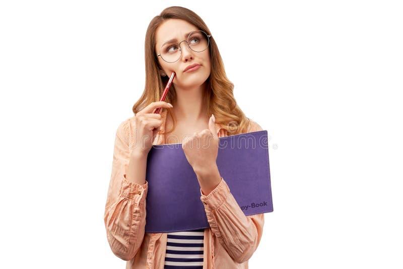 Het mooie jonge meisje heeft nadenkende uitdrukking, houdt blocnote met potlood, denkt over het schrijven van poging, draagt opti stock foto