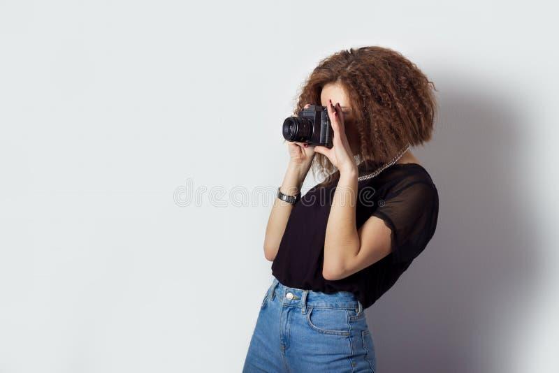 Het mooie jonge meisje hipster maakt de beelden, foto's op de camera in jeans en een zwarte t-shirt in de Studio stock afbeelding