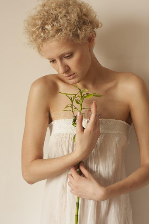 Het mooie jonge meisje houdt in handen zacht groene spruit fondness stock fotografie