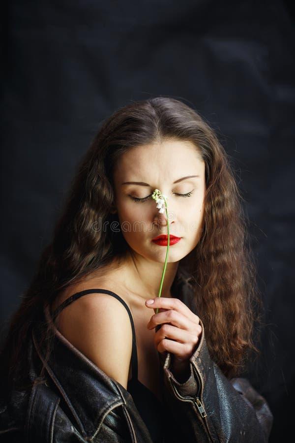 Het mooie jonge meisje in leerjasje het stellen in Studio op zwarte isoleerde achtergrond In de handen van vrouwenbloem royalty-vrije stock afbeeldingen