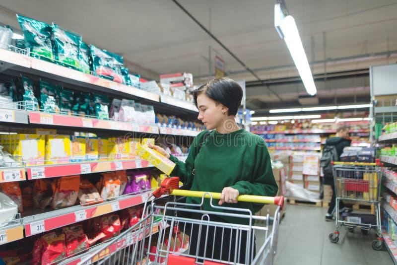 Het mooie jonge meisje met boodschappenwagentjes kiest het winkelen bij een supermarkt Het meisje bekijkt de doos bij de opslag royalty-vrije stock fotografie