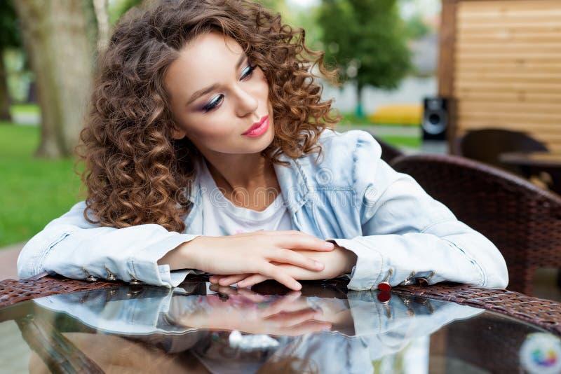 Het mooie jonge meisje met krullend haar zit bij een lijst bij een openluchtdag van de koffiezomer stock foto's