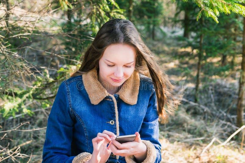 Het mooie jonge meisje met lang donker blond haar in een denimjasje en met een telefoon in haar handen rust in een groen park stock afbeelding
