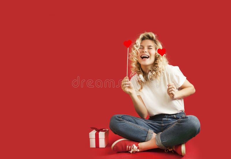 Het mooie jonge meisje met rode harten en een witte gift met een boog zit in de volledige groei op de Dag van een geïsoleerde rod stock afbeelding