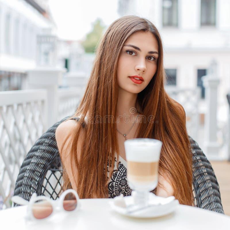 Het mooie jonge meisje met rode lippen rust in een koffie op zonnig DA royalty-vrije stock afbeeldingen