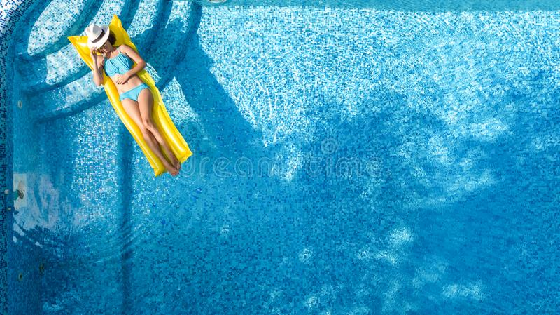 Het mooie jonge meisje ontspannen in zwembad, zwemt op opblaasbare matras en heeft pret in water op familievakantie royalty-vrije stock afbeeldingen