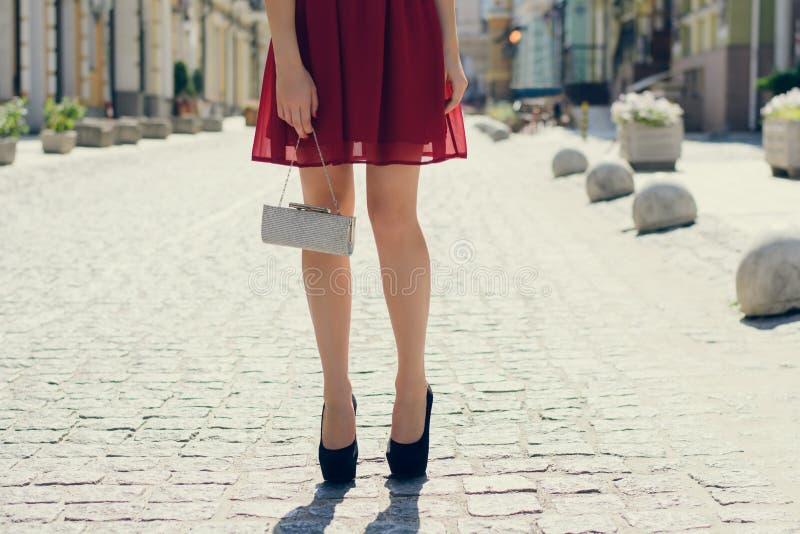 Het mooie jonge meisje in rode avondjurk met zak in handen wacht royalty-vrije stock foto's