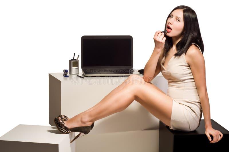 Het mooie jonge meisje schildert haar lippen met lippenstiftzitting bij de computer in het bureau stock afbeeldingen