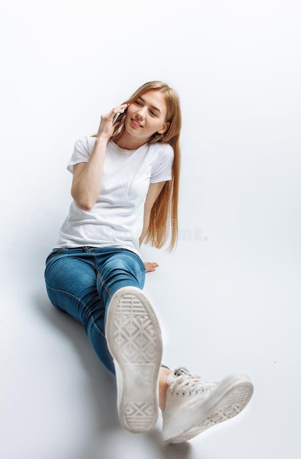 Het mooie jonge meisje spreken op de telefoon, in de Studio, isoleerde achtergrond, vrolijk en positief stock afbeeldingen