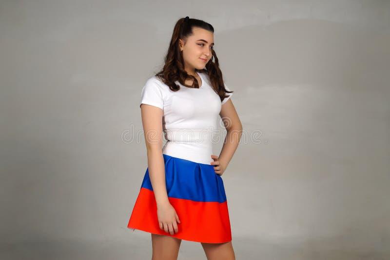 Het mooie jonge meisje stellen in een Russische vlagrok royalty-vrije stock fotografie
