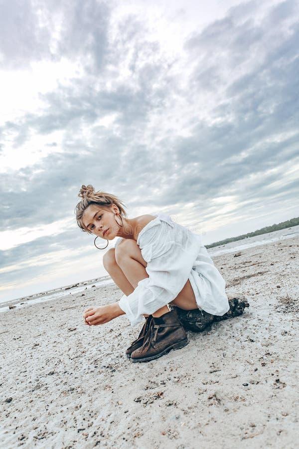 Het mooie jonge meisje van de bohostijl op het strand bij zonsondergang jong Na stock foto's