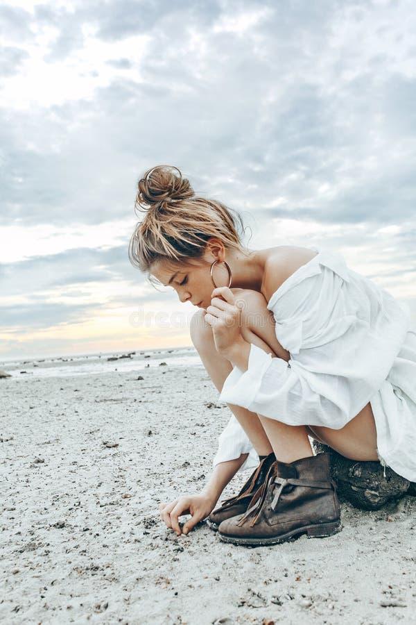 Het mooie jonge meisje van de bohostijl op het strand bij zonsondergang jong Na royalty-vrije stock afbeeldingen