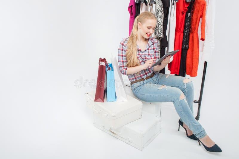 Het mooie jonge meisje verspilt tijd in boutique stock fotografie