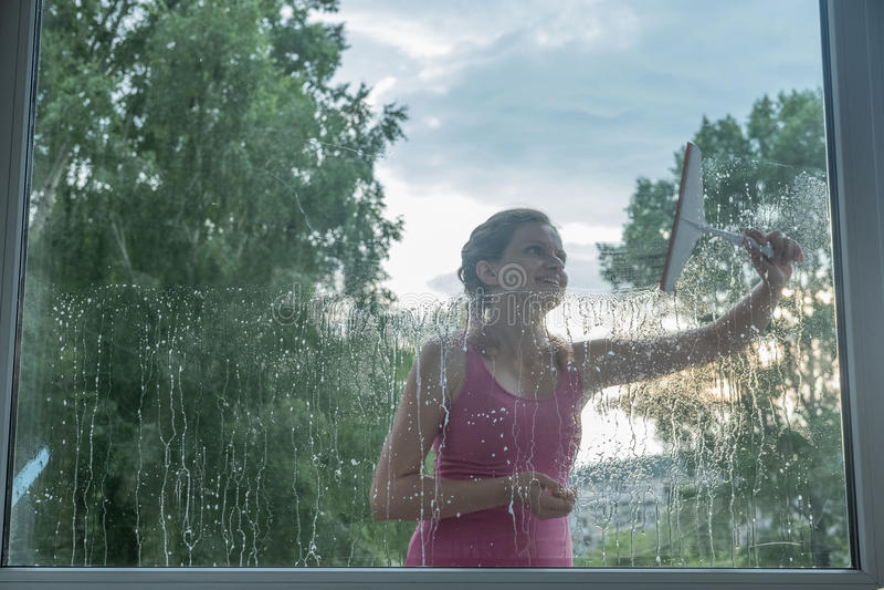 Het mooie jonge meisje wast een venster in een baksteenhuis stock fotografie