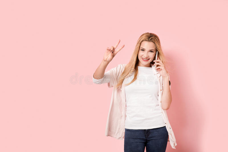 Het mooie jonge meisje zegeviert terwijl het spreken royalty-vrije stock fotografie