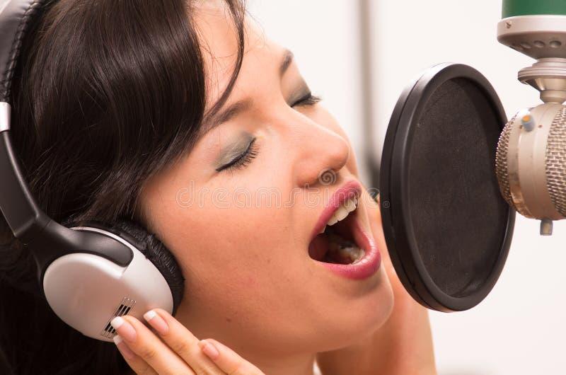 Het mooie jonge meisje zingen in muziekstudio stock afbeeldingen