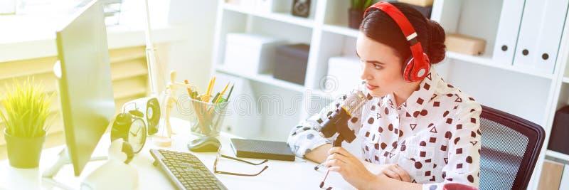 Het mooie jonge meisje zit in hoofdtelefoons en met een microfoon bij het bureau in het bureau royalty-vrije stock foto's