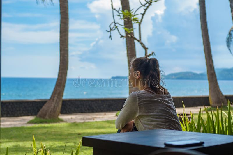 Het mooie jonge meisje zit op de veranda de bungalow de afstand op het oceaanstrand in het eiland Indonesië van Bali onderzoekt royalty-vrije stock foto