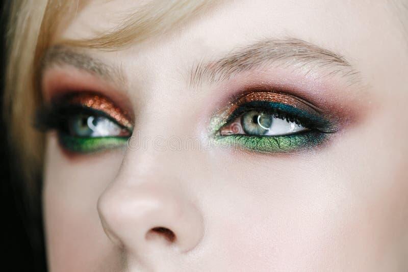 Het mooie jonge model met groen-bruine rokerige oogschaduwavond maakt omhoog, perfecte huid Het portret van het close-upgezicht royalty-vrije stock fotografie