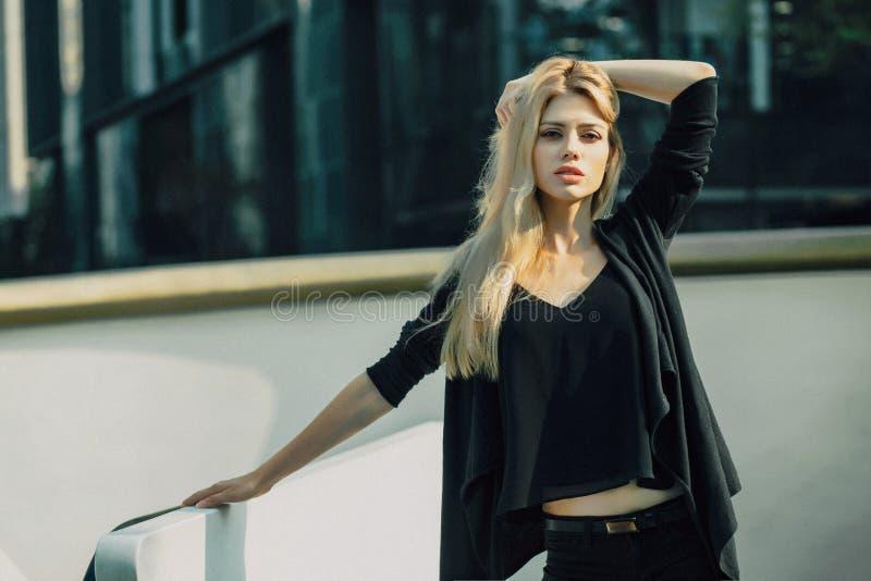 Het mooie jonge modelvrouw stellen in modern architectuurmilieu stock afbeeldingen