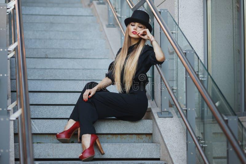 Het mooie jonge modieuze vrouw stellen in zwarte reeks, rode schoenen met hoge hielen en zwarte hoed De Stijl van de mode Stedeli royalty-vrije stock fotografie