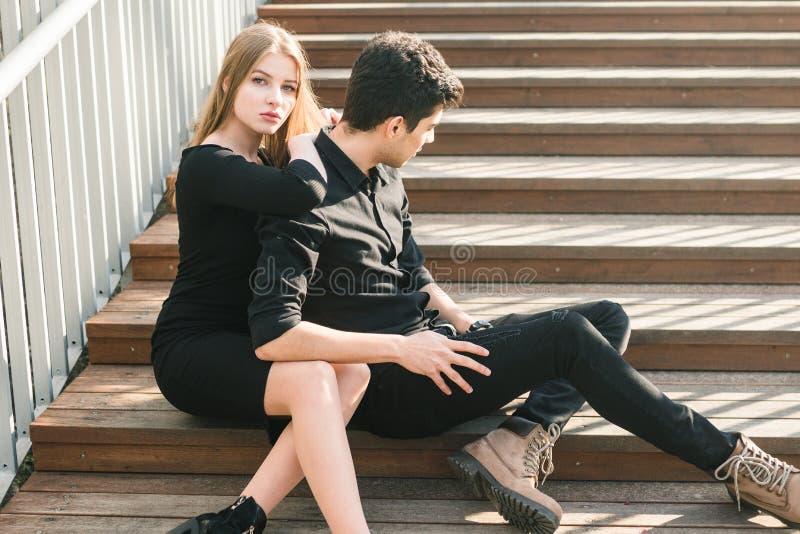 Het mooie jonge multiraciale paar, studentenpaar in liefde, zit houten trap in de stad De mooie Turkse donkerbruine kerel koester royalty-vrije stock afbeelding