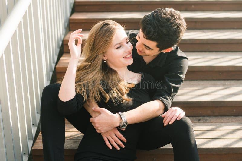Het mooie jonge multiraciale paar, studentenpaar in liefde, zit houten trap in de stad De mooie Turkse donkerbruine kerel koester stock foto