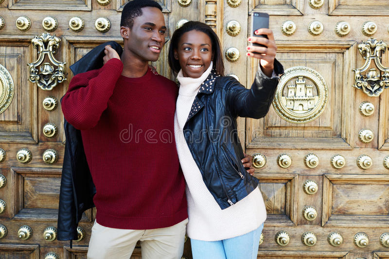 Het mooie jonge paar die op een een stadsman en vrouw lopen hield op om een beeld met Smartphone te nemen royalty-vrije stock afbeeldingen