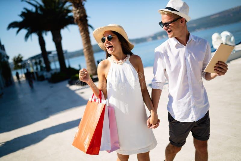 Het mooie jonge paar het genieten van samen winkelen en reis, die pret hebben stock afbeelding