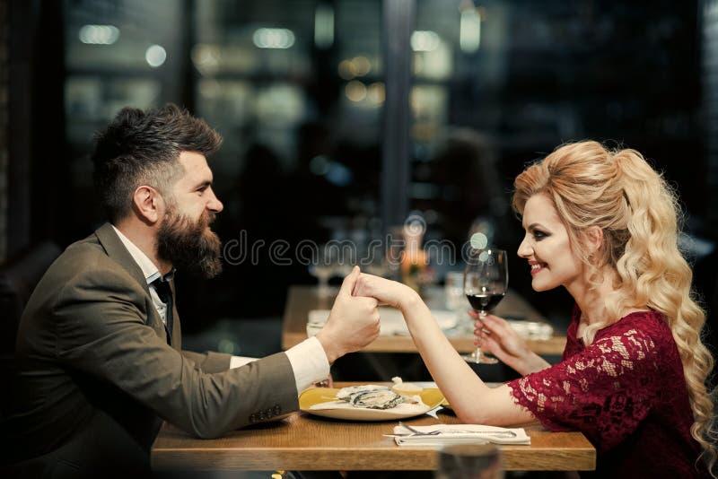 Het mooie jonge paar houdt glazen champagne en glimlacht terwijl het vieren bij bar royalty-vrije stock foto's