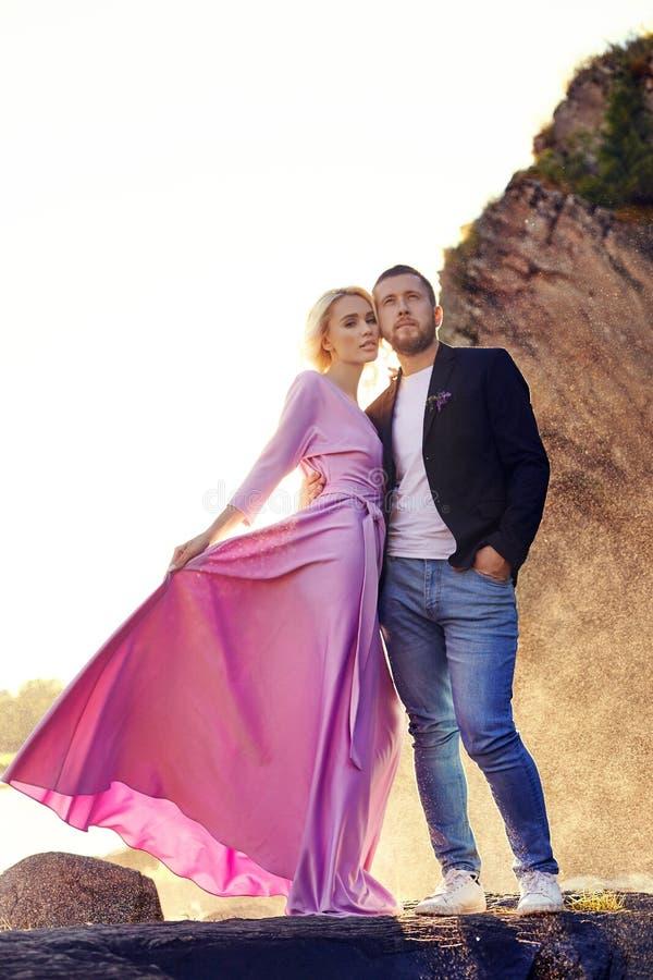 Het mooie jonge paar koestert en bekijkt weg en elkaar die van een romantische datum op de rivier genieten De status van de man e royalty-vrije stock afbeeldingen
