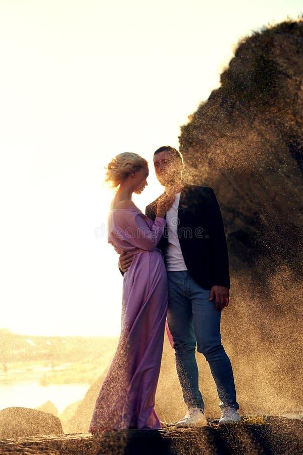 Het mooie jonge paar koestert en bekijkt weg en elkaar die van een romantische datum op de rivier genieten De status van de man e royalty-vrije stock foto