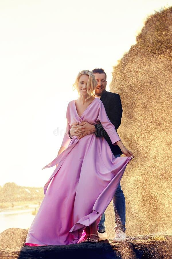 Het mooie jonge paar koestert en bekijkt weg en elkaar die van een romantische datum op de rivier genieten De status van de man e royalty-vrije stock foto's