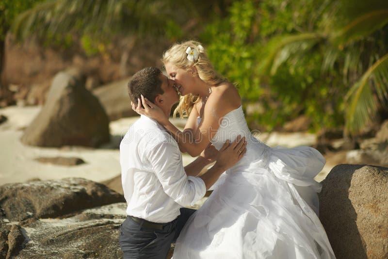 Het mooie jonge paar kussen op zonsondergang, die zich blootvoets op B bevinden stock afbeeldingen