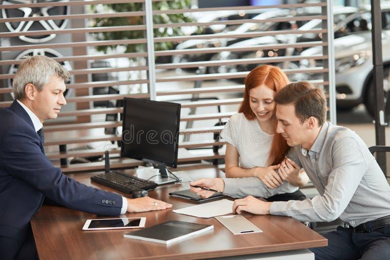 Het mooie jonge paar ondertekent documenten op het kantoor van het autohandel drijven royalty-vrije stock afbeelding