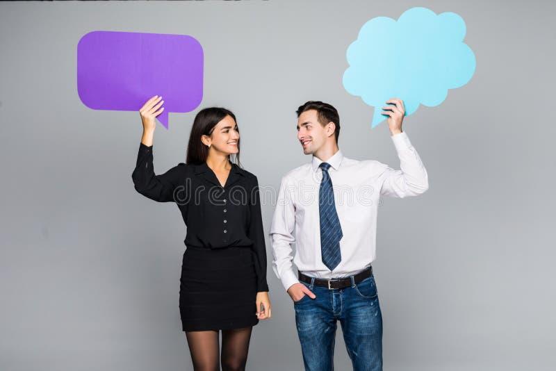 Het mooie jonge paar in vrijetijdskleding houdt kleurrijke toespraakbellen, het bekijken camera en het glimlachen royalty-vrije stock foto's