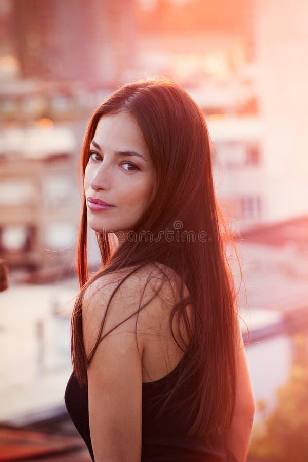Het mooie jonge portret van de stadsvrouw bij dichte zonsondergang de zomer royalty-vrije stock fotografie