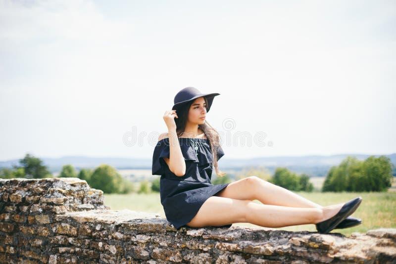 Het mooie jonge, sexy geklede vrouwenmodel van brunette met donkere huid zwarte korte kleding en de hoed met gebieden, fashionabl stock foto