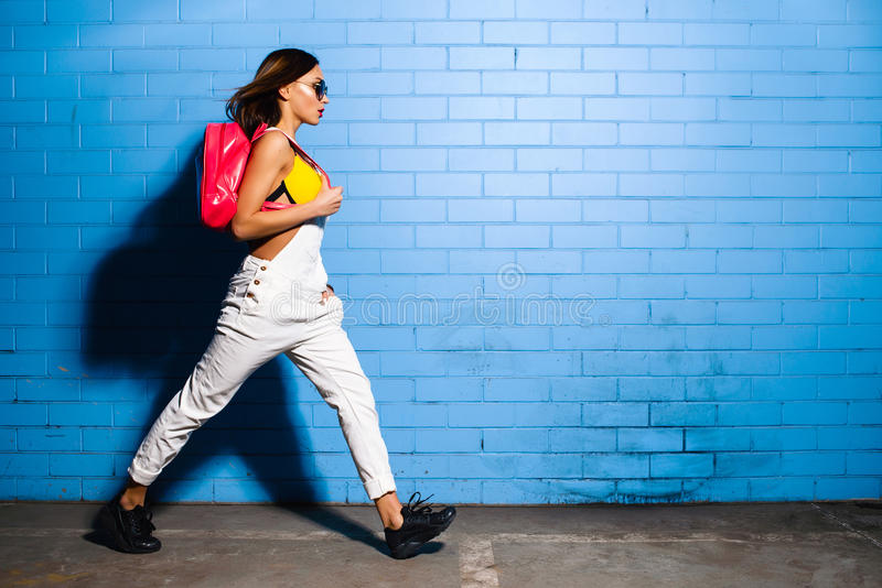Het mooie jonge sexy hipstermeisje gaat dichtbij stedelijke blauwe muurachtergrond in geel zwempak stock foto