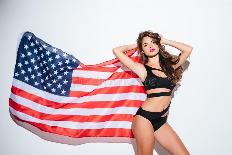Het mooie jonge sexy meisje stellen in bikini met Amerikaanse vlag royalty-vrije stock foto's