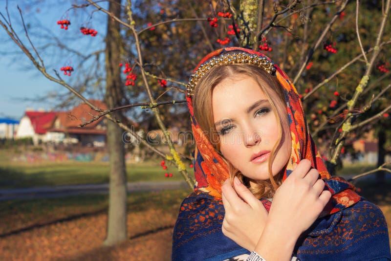 Het mooie jonge tedere bevallige meisje in gekleurde sjaal op haar hoofd met een mooie gouden band met een zachte make-up bevindt royalty-vrije stock foto's