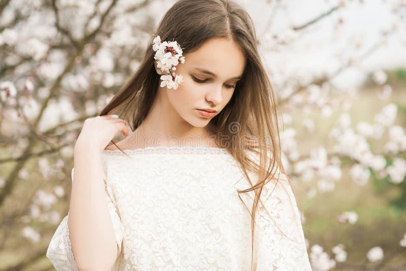 Het mooie jonge tedere meisje in bloesemtuin op een de lentedag, bloembloemblaadjes die van de boom vallen, sloot haar ogen en he stock foto