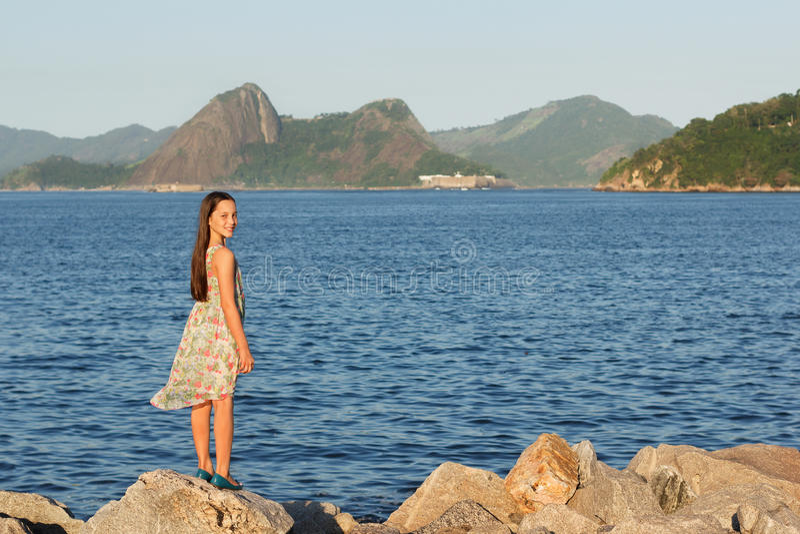Het mooie jonge tienermeisje glimlachen, die zich op stenen dichtbij overzees i bevinden stock foto