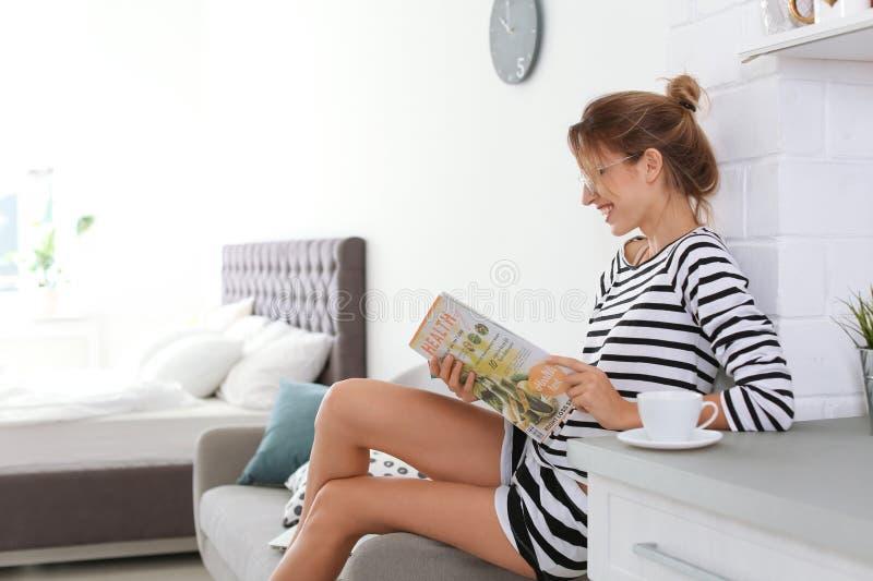 het mooie jonge tijdschrift van de vrouwenlezing stock foto